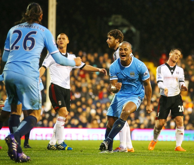 Vincent Kompany celebrates scoring their second goal with Martin Demichelis of Manchester City