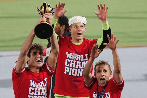 Javier Martinez (L) of Germany's Bayern Munich holds the trophy as he celebrates with goalkeeper Manuel Neuer (C) and Rafinha after winning their 2013 FIFA Club World Cup final