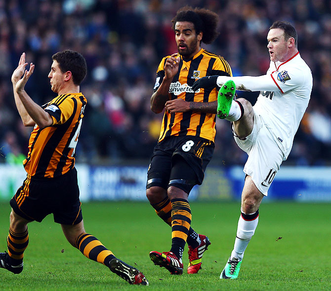Wayne Rooney (right) of Manchester United shoots and scores his sides second goal against Hull City