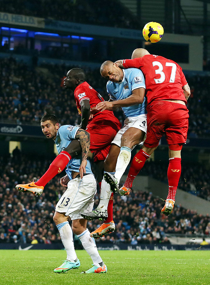 Martin Skrtel of Liverpool goes up for the ball with Vincent Kompany of Manchester City during their match at the Etihad Stadium on Thursday