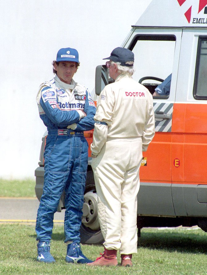Ayrton Senna of Brazil talks with chief FIA medical officer Dr Sid Watkins after Roland Ratzenberger's fatal crash