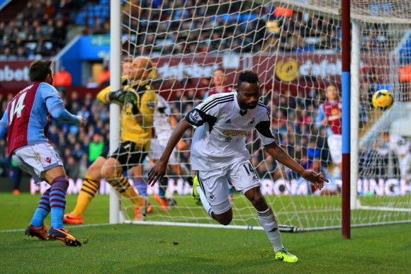 Roland Lamah of Swansea City turns to celebrate after scoring their first goal past Brad Guzan of Aston Villa during the Barclays Premier League match