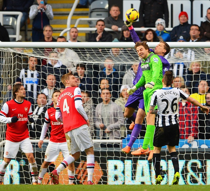 Goalkeeper Wojciech Szczesny of Arsenal punches clear as he is challenged by Newcastle goalkeeper Tim Krul