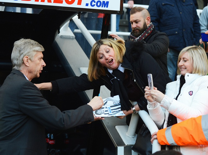 Arsene Wenger, manager of Arsenal signs an autograph