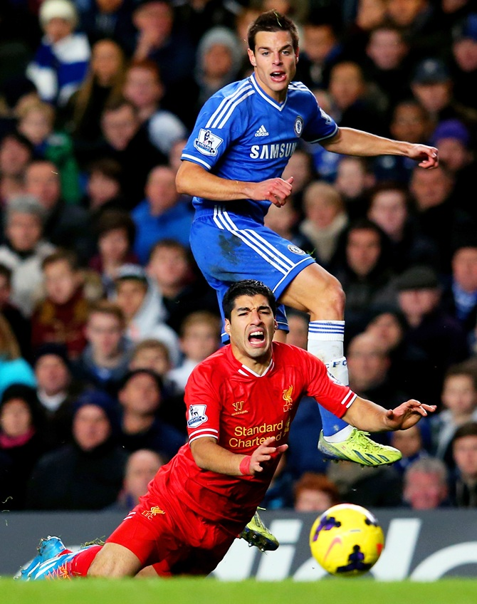 Luis Suarez of Liverpool goes to ground after the challenge from Cesar Azpilicueta of Chelsea
