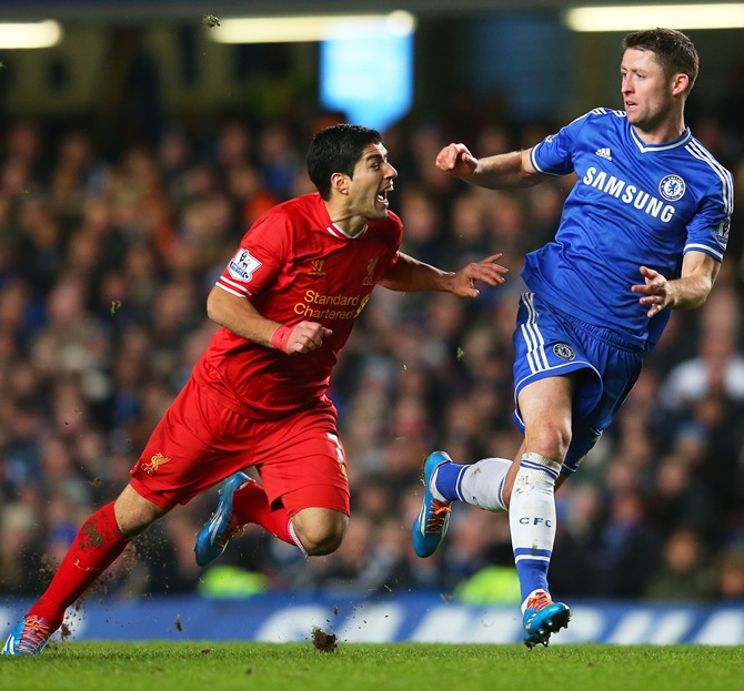 Luis Suarez of Liverpool goes down after contact with Gary Cahill of Chelsea