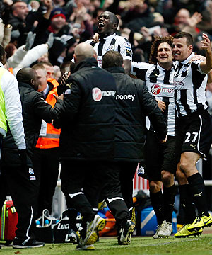Moussa Sissoko (centre) of Newcastle celebrates his winning goal with teammates and staff during their match against Chelsea on Saturday