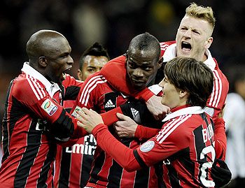 AC Milan's Mario Balotelli (centre) celebrates with teammates after scoring his second goal from the penalty spot on Sunday