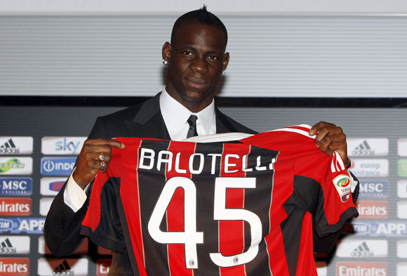 Italy's Mario Balotelli, newly signed player for AC Milan, poses for a photo with his jersey at the San Siro stadium in Milan