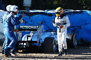 Mercedes GP's Lewis Hamilton walks away from his car after crashing into the gravel at turn six during Formula One winter testing at Circuito de Jerez on Wednesday