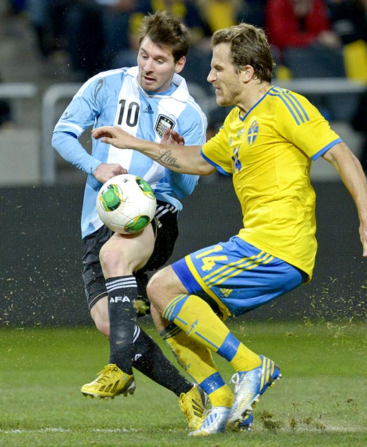 Argentina captain Lionel Messi in a tussle for the ball against Sweden's Tobias Hysen