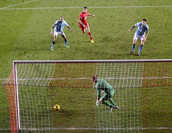 Manchester City's Gareth Barry (right) scores an own goal