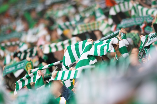 Fans hold aloft green scarves