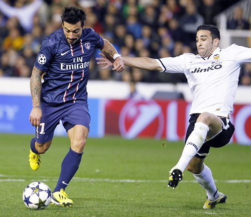 Paris Saint Germain's Ezequiel Lavezzi (left) is challenged by Valencia's Adil Rami