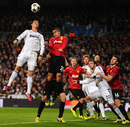 Cristiano Ronaldo of Real Madrid and Robin van Persie of Manchester United go up for a header
