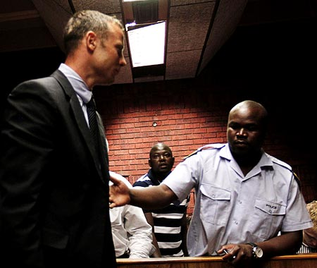 Oscar Pistorius is escorted by police during his court appearance in Pretoria