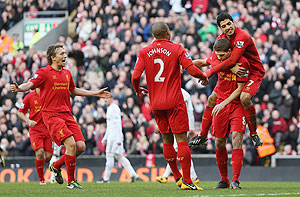 Liverpool's Steven Gerrard celebrates with Luis Suarez, Glen Johnson and Lucas after scoring the first goal from the penalty spot against Swansea on Sunday