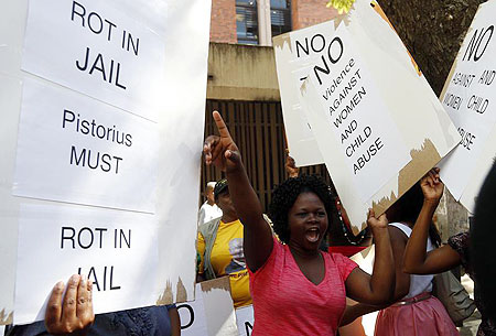 Women protest outside the Pretoria Magistrates court, during the bail application hearing of South African athlete Oscar Pistorius on Tuesday