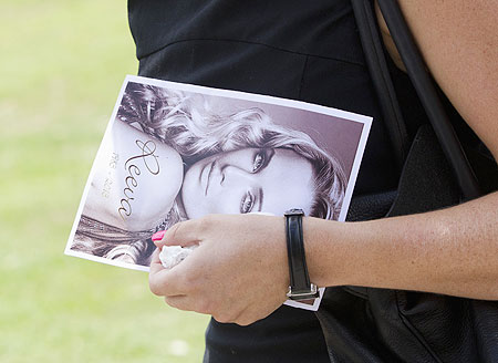 A mourner leaves, holding a picture of model Reeva Steenkamp, after her memorial service at the Victoria Park Crematorium in Port Elizabeth on Tuesday