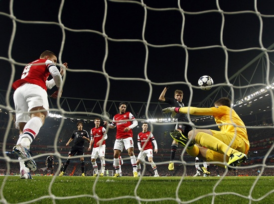 Bayern Munich's Thomas Muller (centre) scores a goal past Arsenal's goalkeeper Wojciech Szczesny