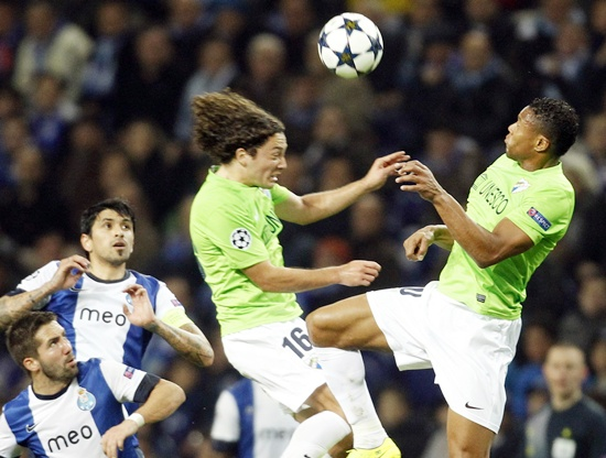 Porto's players (left) watch as Malaga's Manuel Iturra (centre) and Julio Baptista jump for the ball