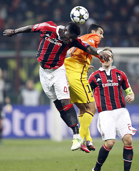 AC Milan's Sulley Muntari (left) and Barcelona's Pedro in an aerial challenge during their Champions League match on Wednesday