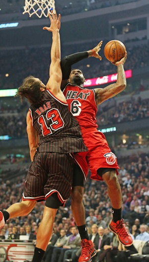 LeBron James of the Miami Heat goes up for a shot against Joakim Noah of the Chicago Bulls 