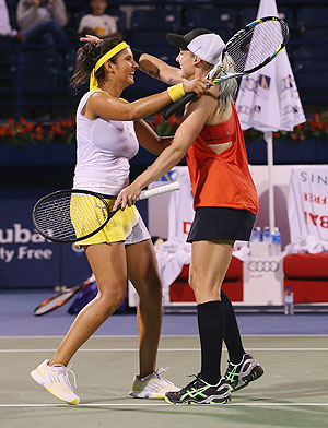 Bethanie Mattek-Sands of USA (right) celebrates with partner Sania Mirza of India after defeating Nadia Petrova of Russia and Katerina Srebotnik of Slovenia to win win the WTA Dubai Duty Free Tennis Championship doubles final on Saturday