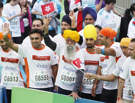 British Indian marathon runner Fauja Singh (centre), 101, carrying a Hong Kong flag, and accompanied Indian runners