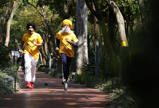 Fauja Singh (right) jogs with his coach Harmander Singh