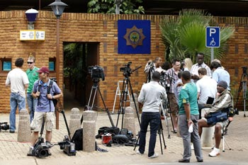 South African journalist wait outside court