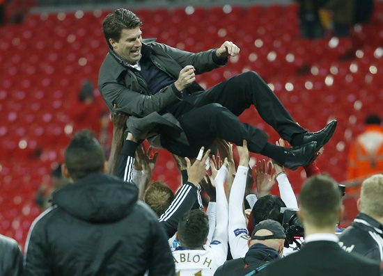 Swansea City's manager Michael Laudrup is tossed in the air by the players