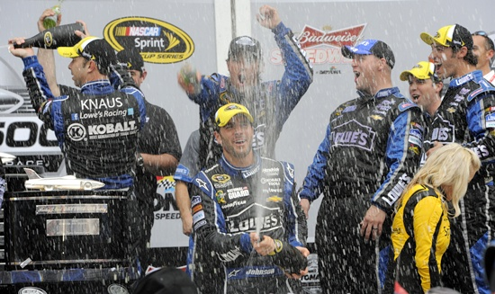 Driver Jimmie Johnson celebrates in victory lane with a bottle of champagne