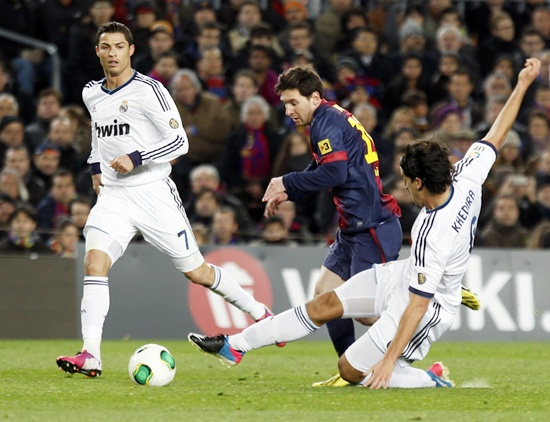 Barcelona's Lionel Messi (centre) is challenged by Real Madrid's Sami Khedira as Real Madrid's Cristiano Ronaldo (left) looks on