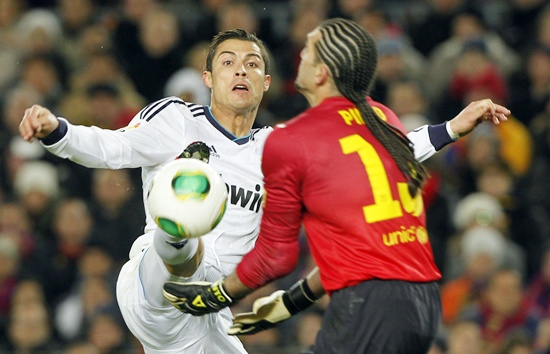Real Madrid's Cristiano Ronaldo (left) chases Barcelona's goalkeeper Jose Manuel Pinto
