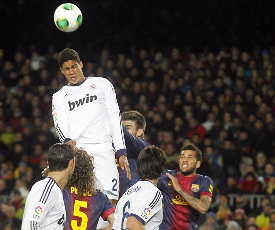 Real Madrid's Rafael Varane heads the ball to score a goal against Barcelona