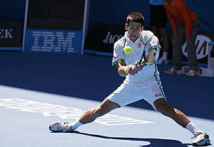 Novak Djokovic of Serbia hits a return to Paul-Henri Mathieu of France on Monday