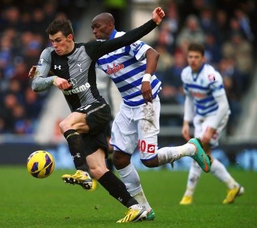 Gareth Bale (L) of Tottenham Hotspur holds off the challenge of Stephane Mbia (R) of Queens Park Rangers during the Barclays Premier League match