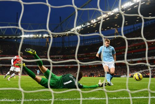 Edin Dzeko of Manchester City shoots past Wojciech Szczesny of Arsenal to score their second goal during the Barclays Premier League match between Arsenal and Manchester City