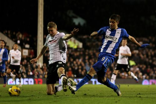 Franco Di Santo of Wigan shoots on goal past the challenge from Brede Hangeland of Fulham during the Barclays Premier League match between Fulham and Wigan Athletic