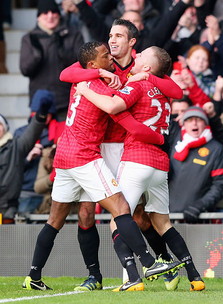 Manchester United's Robin van Persie celebrates with teammates Patrice Evra (left) and Tom Cleverley after scoring the opening goal against Liverpool