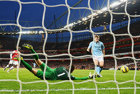 Edin Dzeko of Manchester City shoots past Wojciech Szczesny of Arsenal to score their second goal