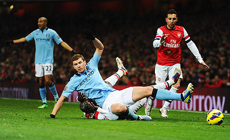 Edin Dzeko of Manchester City is tackled by Bacary Sagna of Arsenal during their Premier League match on Sunday