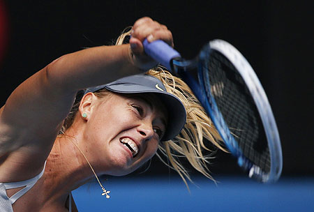 Maria Sharapova of Russia serves to compatriot Olga Puchkova during their first round match on Monday