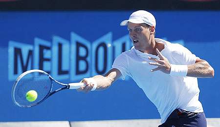 Tomas Berdych of Czech Republic hits a return to Michael Russell of the US during their first round match