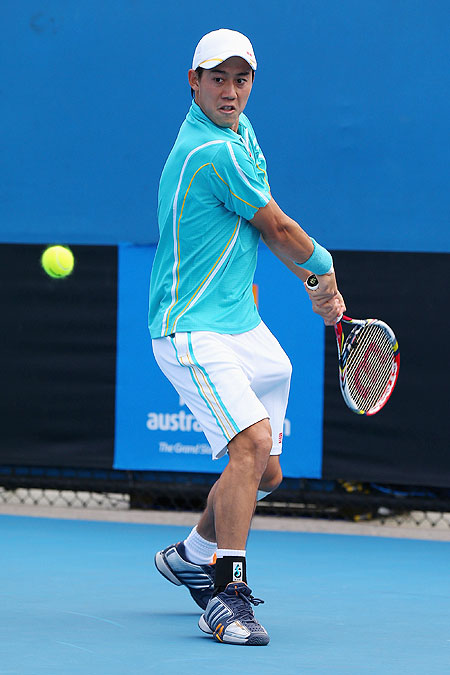 Kei Nishikori of Japan plays a backhand in his first round match against Victor Hanescu of Romania
