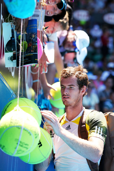 Andy Murray of Great Britain signs an autograph after winning