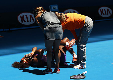 Edina Gallovits-Hall of Romania and an offical check on Serena Williams of the US after she falls over during their women's singles match