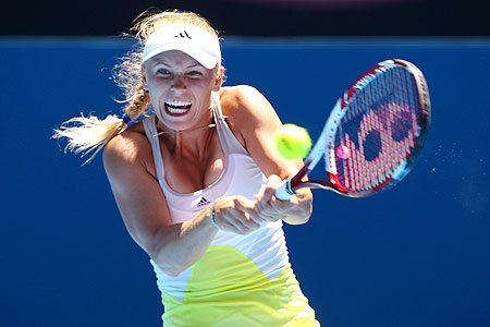 Caroline Wozniacki of Denmark plays a backhand in her first round match against Sabine Lisicki of Germany