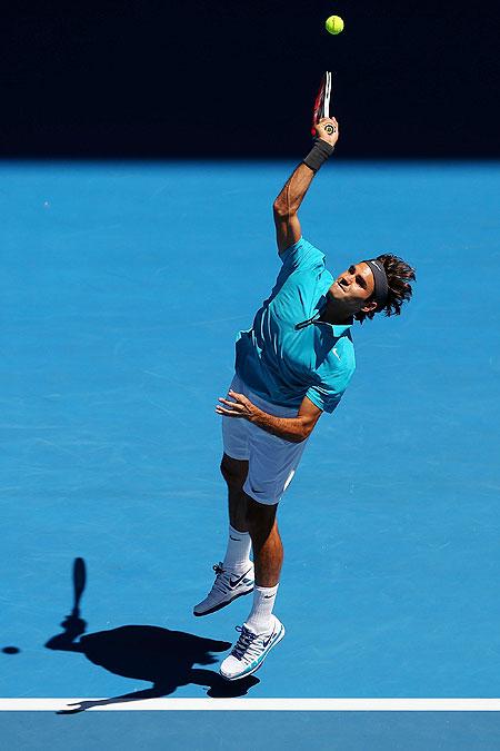 Roger Federer serves to France's Benoit Paire
